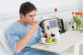 foto of hospital gown  - Young man having healthy food on hospital bed - JPG