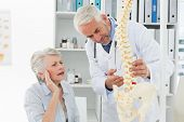 Male doctor explaining the spine to senior patient at medical office