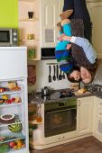 Mother with son stand upside down in the kitchen with open fridge