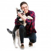 Happy women with her puppy Husky in the studio. Isolated on white background
