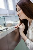 stock photo of jewel-case  - Close up of girl looking at jewelry in window case at jeweler - JPG