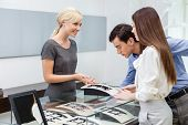 stock photo of jewel-case  - Salesperson helps couple to select jewelry at jeweler - JPG