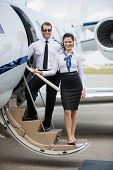 Full length portrait of confident airhostess and pilot standing on ladder of private jet at airport
