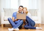 love, family, technology, internet and happiness concept - smiling happy couple with laptop computer