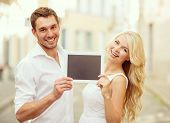 summer holidays, wedding, dating and technology concept - couple with tablet pc in the city