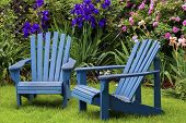 Blue back yard lawn chairs surrounded by a garden of flowers.