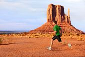 Running man sprinting in Monument Valley. Athlete runner cross country trail running outdoors in amazing nature landscape. Fit male sports model in fast sprint at speed outdoors, Arizona Utah, USA.