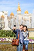 Tourist travel couple taking selfie in Barcelona with smart phone camera. Trendy cool urban city cou