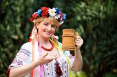 Portrait Happy Ukrainian woman with a wooden mug