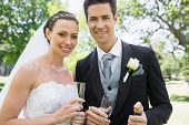 Portrait of newly wed couple holding champagne glasses in garden