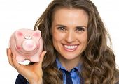 Portrait Of Smiling Business Woman Showing Piggy Bank