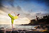foto of natarajasana  - Woman doing yoga on the stone nearby ocean at lighthouse background in Kovalam Kerala India - JPG