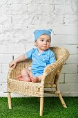 Little Boy Sitting In Wicker Chair