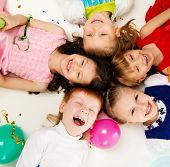 Croup of happy children lying in a circle