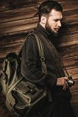 Handsome man wearing cardigan with backpack and vintage camera in house interior