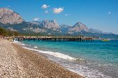 Pier on shingle beach and aquamarine water in popular touristic resort of Kemer on Mediterranean sea in Turkey.