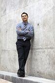 Hispanic Businessman - Leaning On Concrete Wall