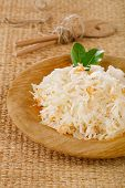 sauerkraut - Sour cabbage -  on wooden bowl with bay leaves
