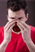 stock photo of sinuses  - Young man complaining about having sinus pain - JPG