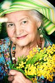 stock photo of mimosa  - Portrait of a beautiful elderly woman with mimosa flowers - JPG