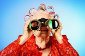 Portrait of an elderly woman in curlers looking ahead through binoculars.
