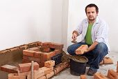 Man Building A Brick Stove Or Fireplace
