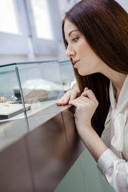 picture of jewel-case  - Close up of girl looking at jewelry in window case at jeweler - JPG