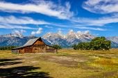 Scenic View Of Grand Teton With Old Wooden Farm