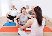 stock photo of senior class  - Rear view of female trainer training senior customers on floor in yoga class - JPG