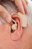 Doctor Inserting Hearing Aid In Senior Man's Ear