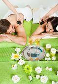 Couple Enjoying Hot Stone Massage At Spa