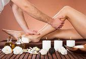 Therapist Massaging Customer's Leg At Beauty Spa