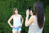 stock photo of two women taking cell phone  - Teenage girl taking photo of her friend with a cell phone - JPG