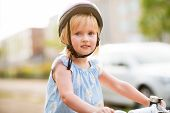 Portrait Of Baby Girl Sitting On Bicycle