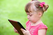 little girl outdoor with tablet pc on hands