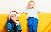 Little Boy In Red Santa Hat With His Brother At Home