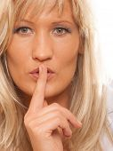picture of hush  - Woman asking for silence or secrecy with finger on lips hush hand gesture - JPG