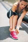 Fitness Young Woman Tying Shoelaces Outdoors