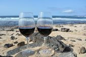 stock photo of canary-islands  - Celebration With Two Glasses Of Red Wine On The Beach Canary Island Spain - JPG