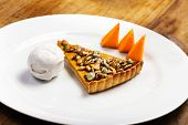 Pumpkin Pie With Whipped Cream And Pumpkin Pieces On White Plate Over Wooden Background.  Beautiful