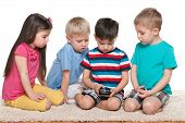 Four Kids With A Gadget On The Carpet