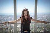 Portrait Of A Beautiful Teenager Girl With Aerial View On Barcelona, Leaning Against A Handrail