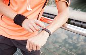 stock photo of sunrise  - Close up view of guy using fitness device outdoors at sunrise - JPG