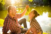 stock photo of love bite  - happy young couple bite grapes and enjoying picnic - JPG