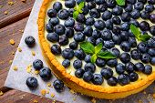 Blueberry Tart on vintage wooden background
