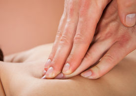 picture of chiropractic  - Closeup of male therapist massaging female customer - JPG
