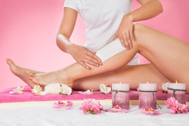 picture of therapist  - Midsection of female therapist waxing customer - JPG