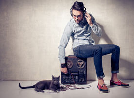 image of outdated  - handsome man and cat listening to music on a magnetophone against grunge wall - JPG