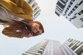 picture of redhead  - Redhead girl with yellow coat listening to music in the city streets