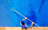 stock photo of top-hat  - young adult man personnel cleaning the pool from leaves